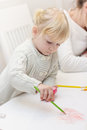 Little girl drawing with colorful crayons Stock Image