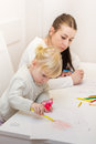 Little girl drawing with colorful crayons mother at home Stock Image
