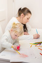 Little girl drawing with colorful crayons mother at home Royalty Free Stock Image