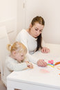 Little girl drawing with colorful crayons mother at home Royalty Free Stock Photo