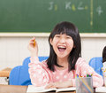 Little girl drawing on her book and having fun in a classroom Stock Photos
