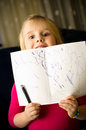 Little girl drawing with pen a cute at home a focused on her children artwork showing her abstract work Stock Images