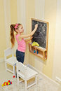 Little girl draws on blackboard with chalk Royalty Free Stock Images