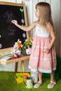 Little girl draws on a blackboard chalk Stock Photo