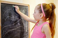 Little girl draws with chalk on blackboard Stock Image