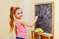 Little girl draws with chalk on blackboard half length portrait of who Royalty Free Stock Photos