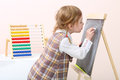 Little girl draws with chalk on chalkboard near colorful abacus in studio Stock Images