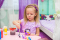 Little girl draws paints at her desk in the room Royalty Free Stock Photo