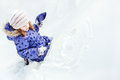 Little girl draws on the snow a smiley face Royalty Free Stock Photo