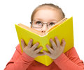 Little girl is dreaming while reading book Royalty Free Stock Photos