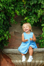 Little girl in a dress blonde on background of green grape leaves Royalty Free Stock Photo