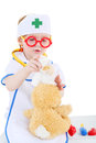 Little girl dressed as nurse bandages head to toy rabbit and in glasses isolated on white background Royalty Free Stock Image