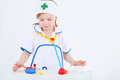 Little girl dressed as nurse plays with toy medical instruments on white background Stock Photo