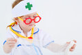 Little girl dressed as nurse spreads bandage on white background Stock Images