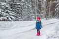 Little Girl dressed in a blue coat and a pink hat and boots throws snow and laughs Royalty Free Stock Photo