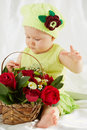 Little girl dressed in greenish clothes and hat sitting on bedding portrait of with wicker basket of flowers Royalty Free Stock Photography