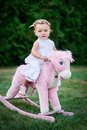 Little girl dressed up as cowgirl playing with toy horse in park Stock Photo