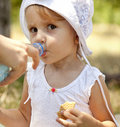 Little girl dring water in the park. Royalty Free Stock Image