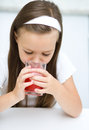 Little girl is drinking cherry juice using straw Stock Photo