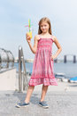 Little girl drinking fruit cocktail outdoors in the summer day. Royalty Free Stock Photo