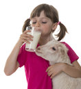 Little girl drinking healthy goat milk and holding Royalty Free Stock Photos
