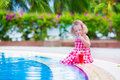 Little girl drinking juice at a swimming pool beautiful cute toddler with curly hair wearing red summer dress sitting water melon Stock Photo