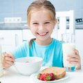 Little girl drinking milk cute smiling in the kitchen Stock Photo