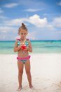 Little girl drinks juice from watermelon on the exotic beach this image has attached release Stock Image
