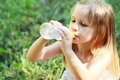 Little girl drinks mineral water in green park Royalty Free Stock Images