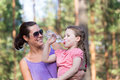 Little girl drinks water outdoors with her mum Stock Photo