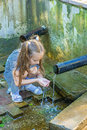 Little girl drinks water from source beautiful in summer city park Stock Photo