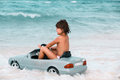Little girl driving car in to the ocean tanned pretty her Stock Images