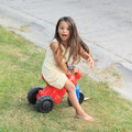 Little girl driving small kids motorbike barefoot in yellow dress a red Stock Photos