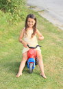 Little girl driving small kids motorbike barefoot in yellow dress a red Royalty Free Stock Photo