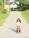 Little girl driving small kids motorbike barefoot in yellow dress a red on asphalt road Stock Images