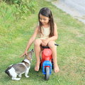 Little girl driving small kids motorbike barefoot in yellow dress a red fondling dog Stock Image
