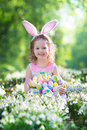 Little girl with easter bunny ears having fun on egg hunt kids in and rabbit costume children searching for eggs in the garden Stock Photos