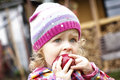 Little girl eating apple in autumn toddler the garden portrait Stock Photo
