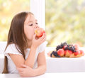 Little girl eating an apple cute Stock Photos