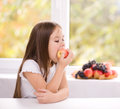 Little girl eating an apple cute Stock Photography