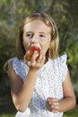 Little girl eating apple outdoors closeup portrait of a Royalty Free Stock Photos