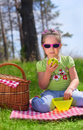 Little girl eating apple at picnic in the woods Stock Photo