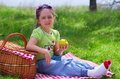 Little girl eating apple at picnic in the woods Royalty Free Stock Photos