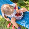 Little girl eating berries the is sitting on a hammock and Royalty Free Stock Photos