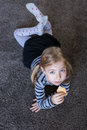 Little girl eating biscuits on the carpet. Repaired girls. Royalty Free Stock Photo