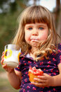 Little girl eating bread and drinks milk outdoors Stock Photography