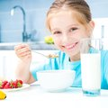 Little girl eating cute cereal and strawberries in the white kitchen Stock Photography