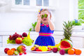 Little girl eating fresh tropical fruit cute curly in a colorful summer dress and berry for healthy breakfast snack in a white Stock Image