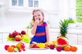 Little girl eating fruit cute curly in a colorful summer dress fresh tropical and berry for healthy breakfast snack in a white Royalty Free Stock Images