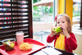 Little girl eating a hamburger in fast food restaurant